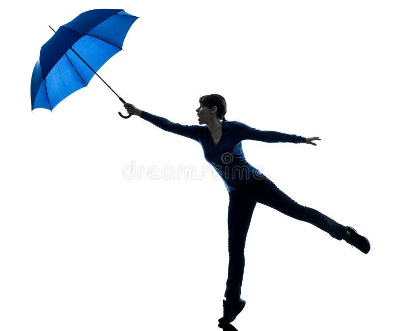 Frau, die durchbrennenschattenbild des Regenschirmwinds hält stockbilder