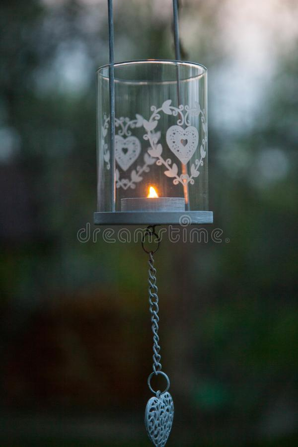 Eine Kerze in einem Glasbecherhalter hängt an der Straße lizenzfreie stockfotos