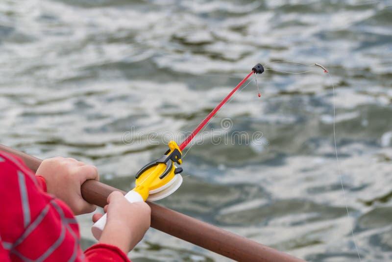 Eine Kind-` s Hand fischt auf einer kleinen Angelrute Ozernaya-Fischen lizenzfreies stockfoto