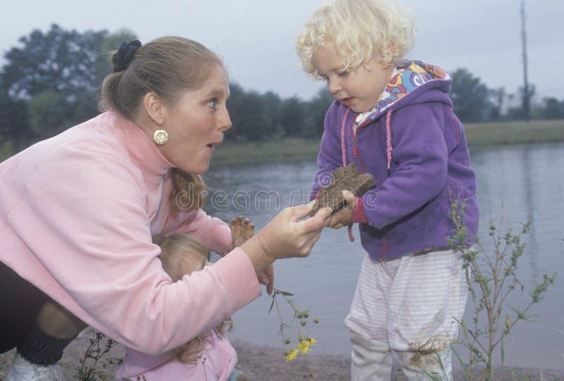 Eine Kinderbetreuungsarbeitskraft, die mit Kindern durch einen See, Washington D spielt C lizenzfreie stockfotos