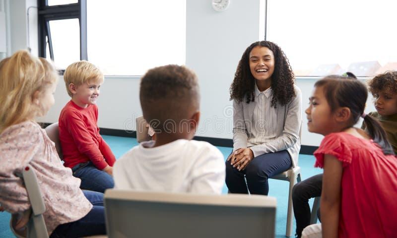 Eine Klasse Säuglingsschulkinder, die auf Stühlen in einem Kreis im Klassenzimmer sprechend mit ihrem weiblichen Lehrer sitzen lizenzfreie stockfotos