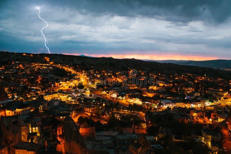 Eine kleine authentische Stadt nannte Goreme in Cappadocia in der Türkei Drastischer nächtlicher Himmel, Sonnenuntergang Blitz üb lizenzfreies stockbild