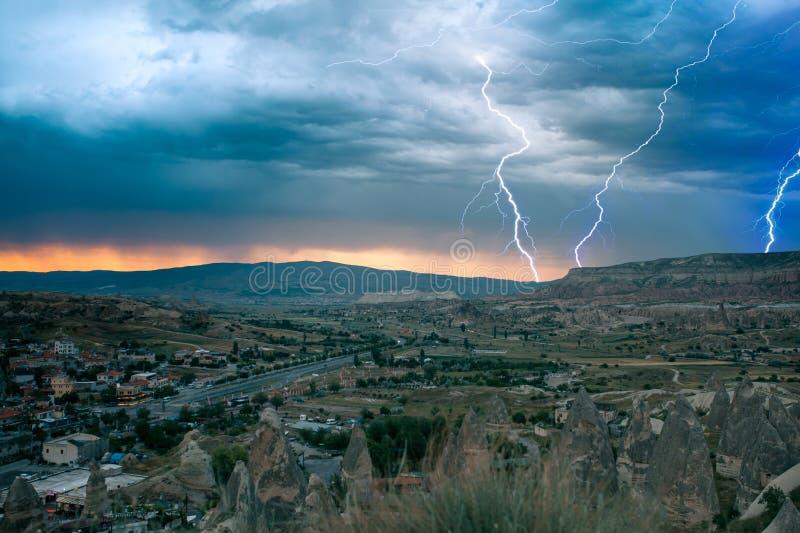 Eine kleine authentische Stadt nannte Goreme in Cappadocia in der Türkei Drastischer nächtlicher Himmel, Sonnenuntergang Blitz üb lizenzfreie stockbilder