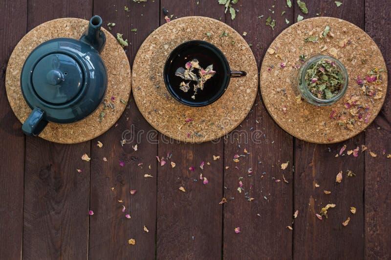 Eine kleine blaue Teekanne, ein Becher Tee und trockener Kräutertee auf einem hölzernen Hintergrund Hypericum perforatum ist gera stockfotos