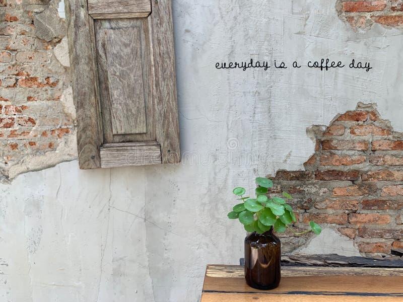 Eine kleine Blume in einem braunen Vase auf dem Tisch Backsteinmauerhintergrund mit orange Sprüngen, Weinlese- und Klassikerarth stockbild