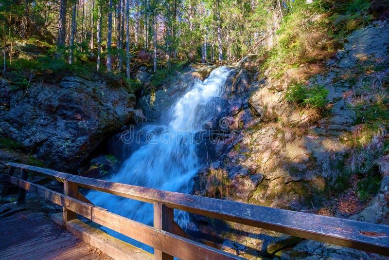 Eine kleine Brücke vor einem Wasserfall stockbilder