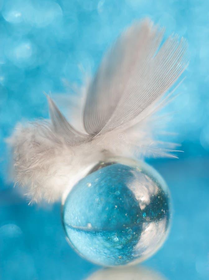 Eine kleine flaumige weiche Feder auf einer Glaskugel, die bokeh auf einem blauen Hintergrund reflektiert stockfotos