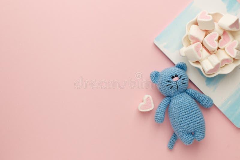 Eine kleine gestrickte Babyspielzeugkatze, ein nitebook und ein Süsseeibisch auf rosa Pastellhintergrund, flache Lage, Draufsich lizenzfreie stockfotografie