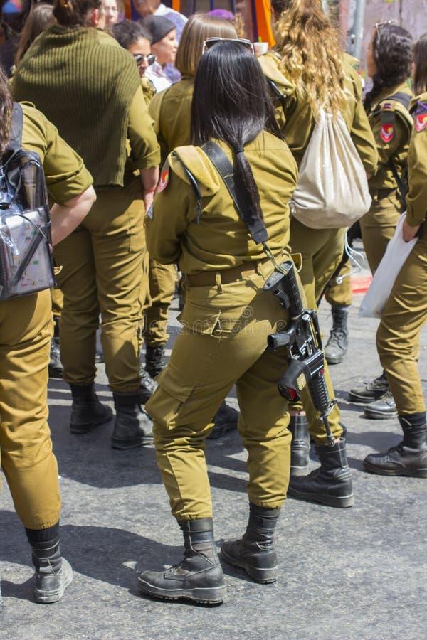 Eine kleine Gruppe dienstfreie weibliche Einberufene der israelischen Armee mit einem Lachen und einem Chat der bewaffneten Wache stockfotos