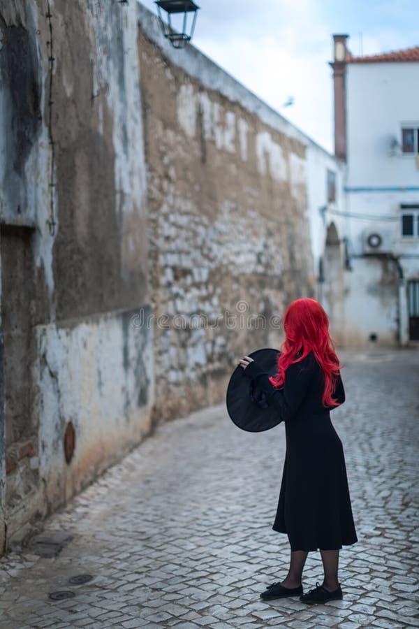 Eine kleine Hexe in einem schwarzen Kleid mit dem roten Haar lizenzfreie stockfotos