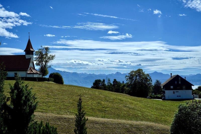 Eine kleine Kapelle auf einem Hügel, Bergen und einem blauen Himmel stockfotos