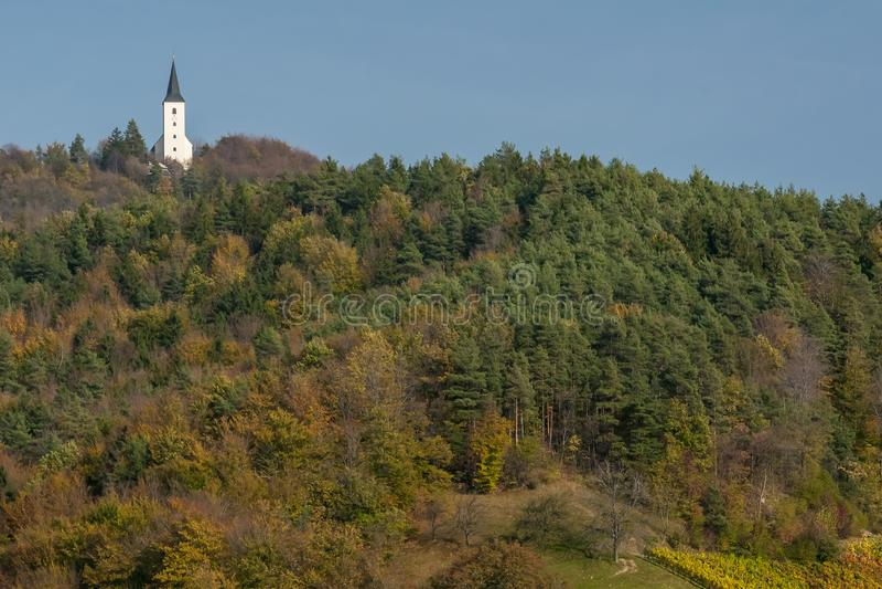Eine kleine Kirche auf einem Hügel im Wald, der durch die typischen Herbstfarben von Zrece, Slowenien, eingefärbt ist lizenzfreies stockbild