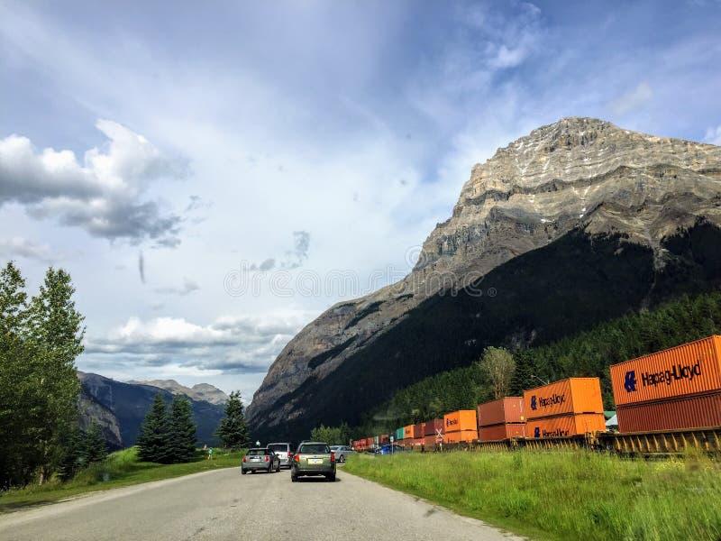 Eine kleine Linie von den Autos, die auf einen Güterzug warten, durch Rocky Mountains außerhalb des Feldes, Britisch-Columbia, Ka stockbild