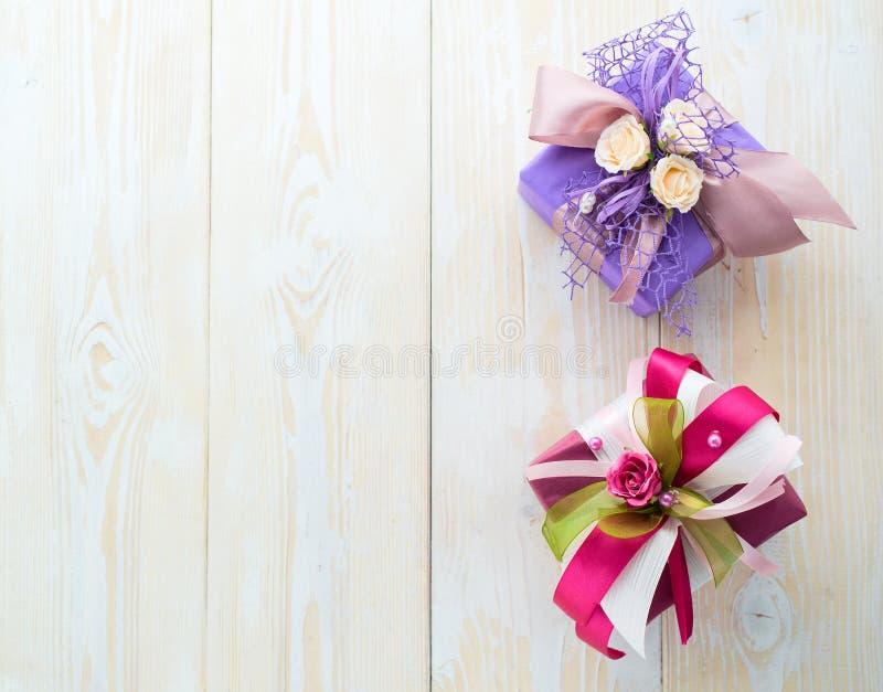 Eine kleine purpurrote Geschenkbox mit Rosen und ribon und der zweite PU lizenzfreie stockfotografie