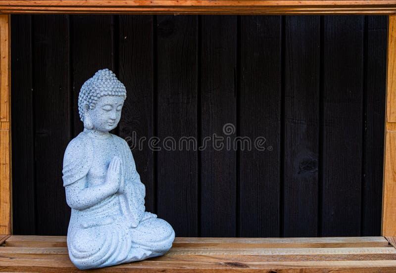 Eine kleine Statue von buddah mit hölzernem Hintergrund stockbild