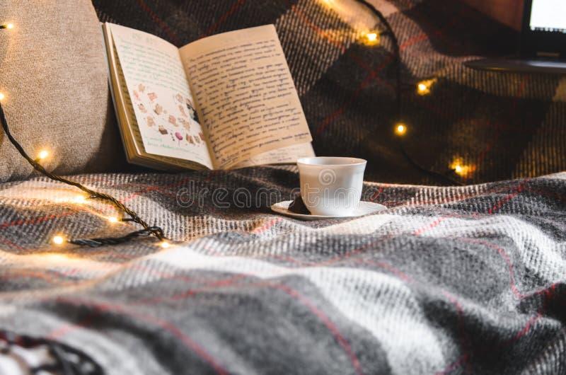 Eine kleine Tasse heißen Tee mit Schokolade auf dem Hintergrund heller Weihnachtslichter, eine warme und gemütliche Atmosphäre de lizenzfreies stockbild