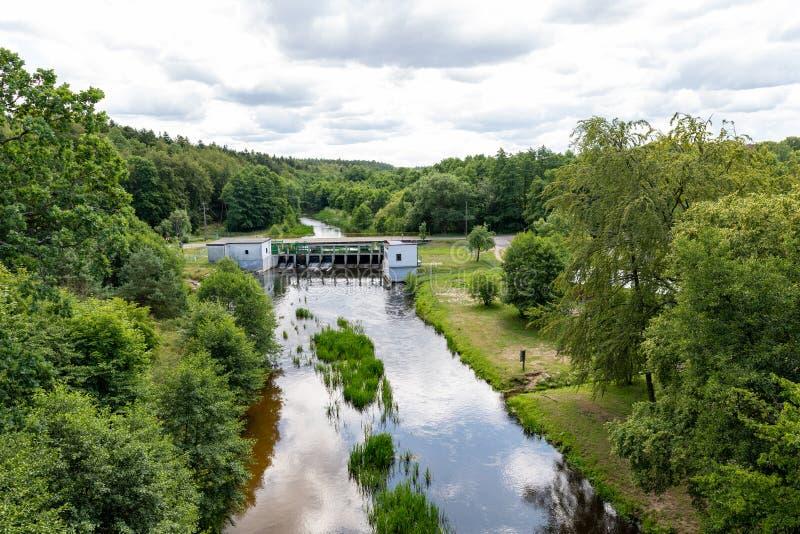 Eine kleine Wasserkraftanlage auf einem kleinen Fluss in Mitteleuropa Eine Sperre mit Turbinen für die Erzeugung des Stroms lizenzfreie stockfotografie