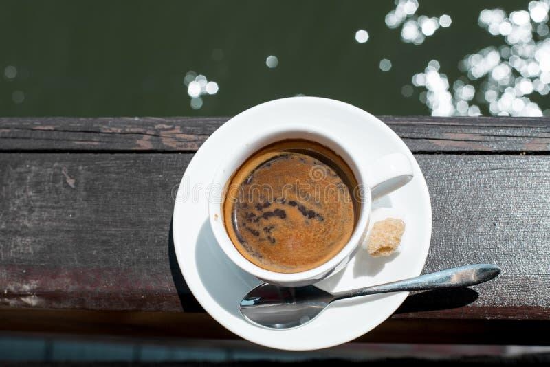 Eine kleine weiße Porzellanespressoschale auf einer Untertasse mit einem Teelöffel und zwei Stücken Zucker stockfoto