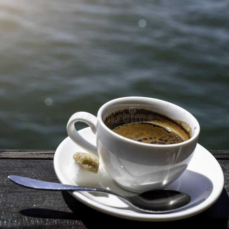 Eine kleine weiße Porzellanespressoschale auf einer Untertasse mit einem Teelöffel und zwei Stücken Zucker lizenzfreies stockfoto