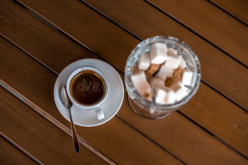 Eine kleine wei?e Porzellanespressoschale auf einer Untertasse mit einem Teel?ffel und zwei St?cken Zucker lizenzfreie stockbilder