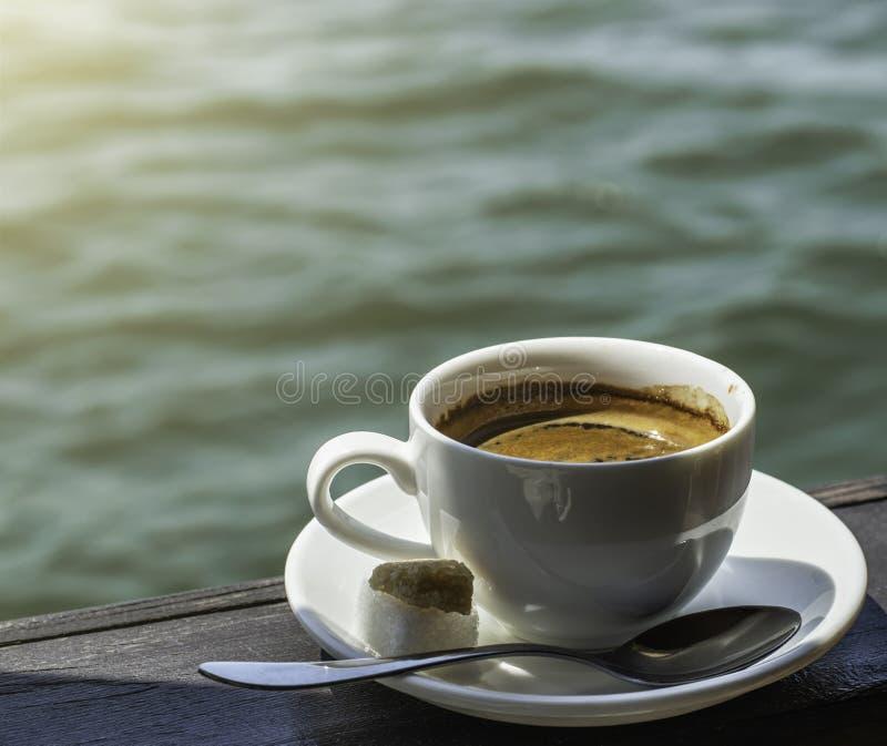Eine kleine wei?e Porzellanespressoschale auf einer Untertasse mit einem Teel?ffel und zwei St?cken Zucker lizenzfreies stockbild