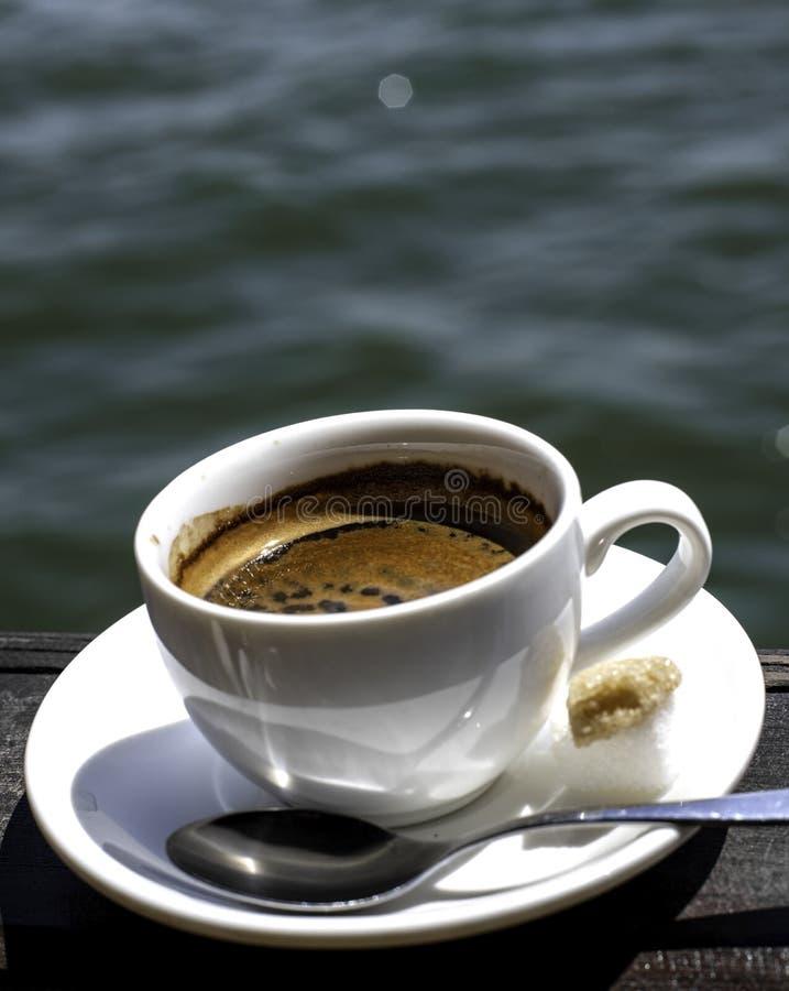 Eine kleine wei?e Porzellanespressoschale auf einer Untertasse mit einem Teel?ffel und zwei St?cken Zucker lizenzfreies stockfoto