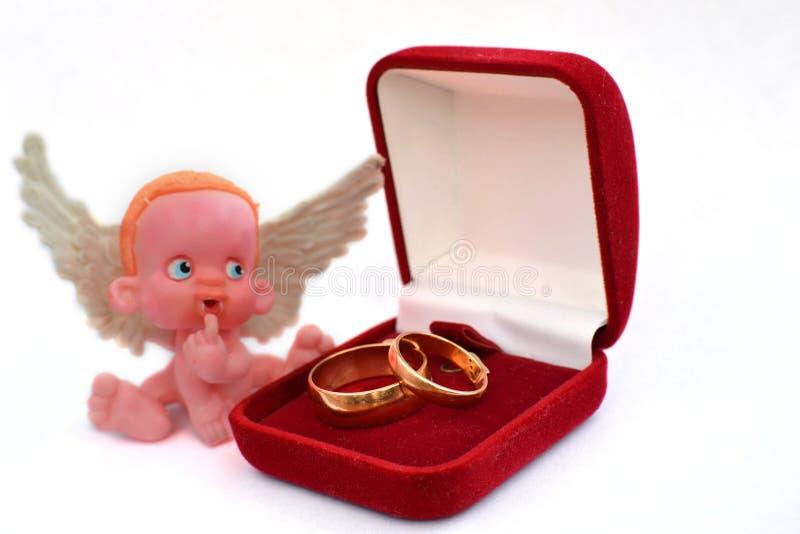 Eine kleine Zahl eines Engels, der nahe einem Schmuckkästchen mit zwei goldenen Eheringen lokalisiert auf Weiß sitzt lizenzfreies stockfoto