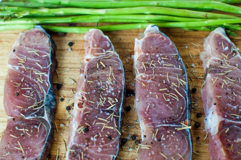 Eine kochende Vorbereitung von rohen Scheiben von Fischen mit Bestandteilen stockfotos