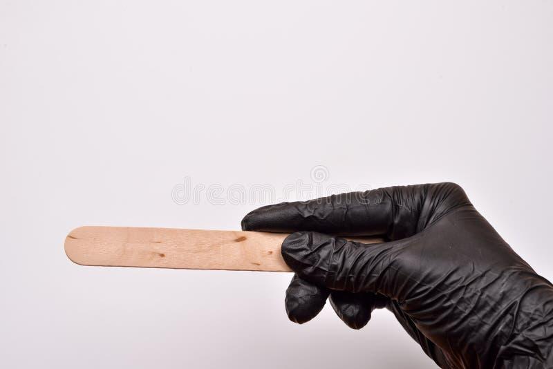 Eine Kosmetikerhand mit dem schwarzen Handschuh, der eine Spachtel für Wachs, p hält stockbild