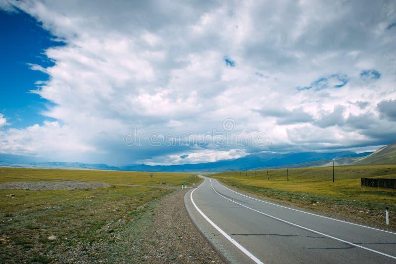 Eine kurvenreiche Straße, die in ein Berggebiet läuft Glatte Asphaltstra?edurchl?ufe zwischen der gelben Ebene zu den entfernten  lizenzfreie stockfotos