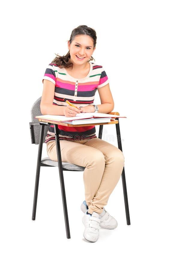 Eine lächelnde Frau, die auf einem Stuhl sitzt und Anmerkungen notiert stockbilder