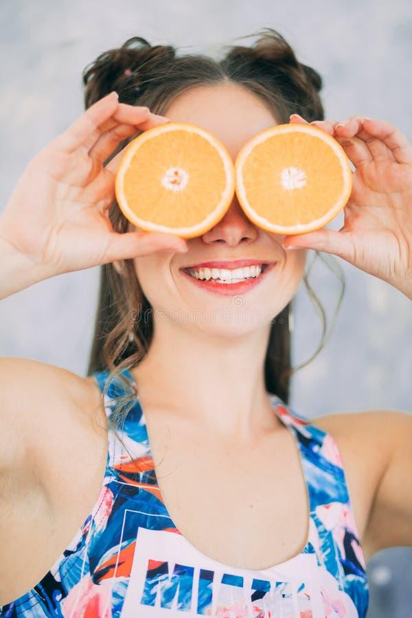 Eine lächelnde Frau hält zwei orange Scheiben nahe ihren Augen lizenzfreie stockbilder