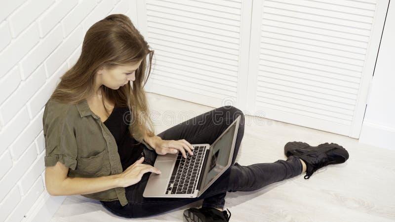 Eine lächelnde hübsche vorbildliche Studentin der Junge arbeitet mit dem Laptop, der auf dem Boden gegen die Wand sitzt lizenzfreies stockbild
