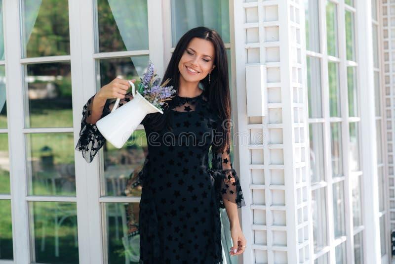 Eine lächelnde helle junge Frau überprüft einen weißen einfachen Vase Blumen und bewundern betrachtet das Design von einem selbst lizenzfreie stockfotografie