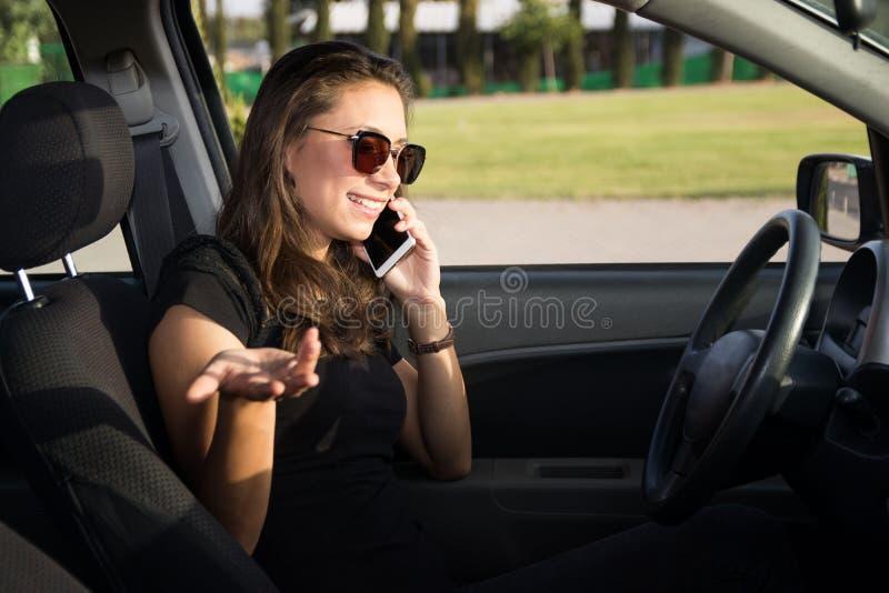 Eine lächelnde junge Frau im Auto spricht am intelligenten Telefon lizenzfreie stockfotos