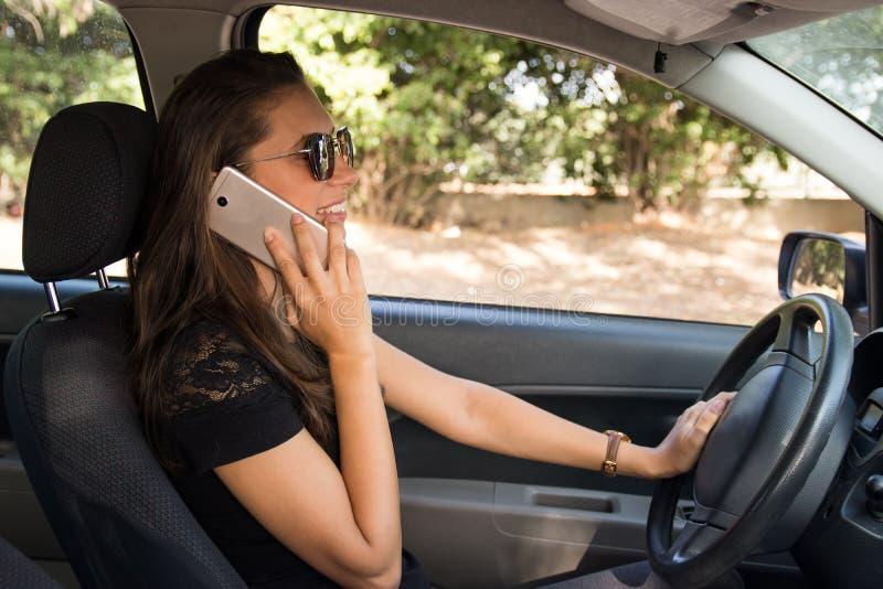 Eine lächelnde junge Frau im Auto spricht am intelligenten Telefon und fährt lizenzfreie stockfotos