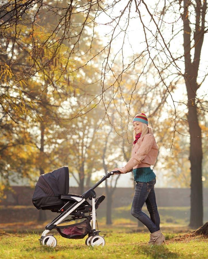 Eine lächelnde Mutter, die mit einem Kinderwagen in einem Park im Herbst aufwirft lizenzfreie stockfotos
