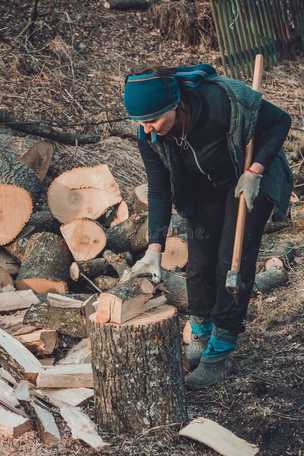 Eine ländliche Frau schießt ein Escheholz für das Ernten für den Winter mit einer Axt lizenzfreie stockfotografie