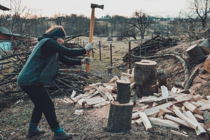 Eine ländliche Frau schießt ein Escheholz für das Ernten für den Winter mit einer Axt lizenzfreies stockbild