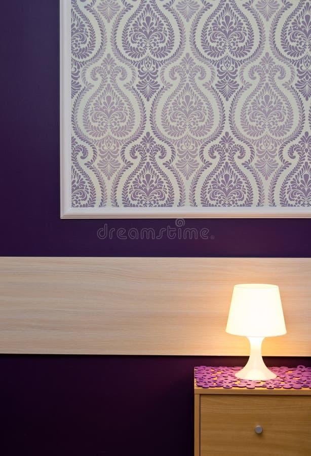 Eine Lampe mit violetter Tapete lizenzfreie stockfotografie