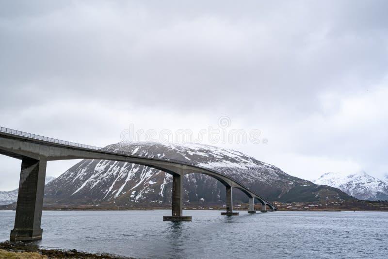 Eine lange Betonbrücke für die Autos und LKWs, die Meer unter bewölktem Himmel kreuzen stockfoto