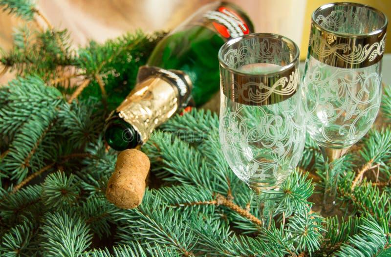 Eine leere Flasche Champagner und ein Korken, der auf Fichtenzweigen, nahe zwei Weingläsern liegt, konzentrieren sich auf das Roh lizenzfreies stockfoto