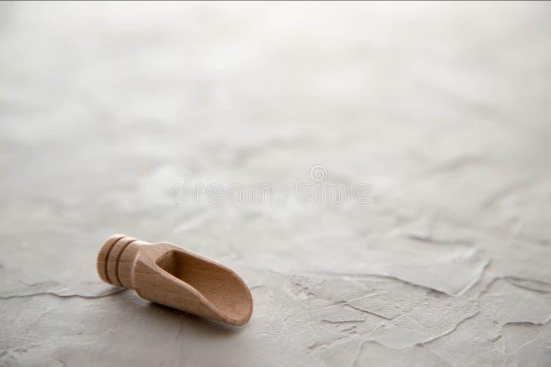 Eine leere hölzerne Schaufel für Gewürze liegt auf einem konkreten Hintergrund Platz f?r Text lizenzfreie stockbilder