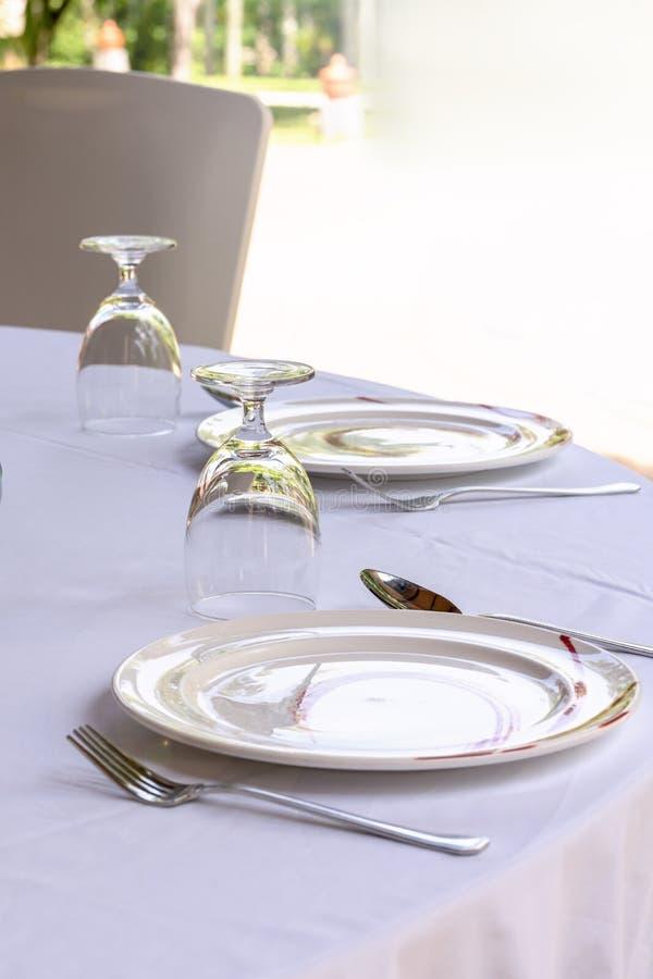 Eine leere Platte auf einer weißen Tabelle Nahaufnahme, vertikal, der leere Raum für ein Menü oder Text lizenzfreies stockbild