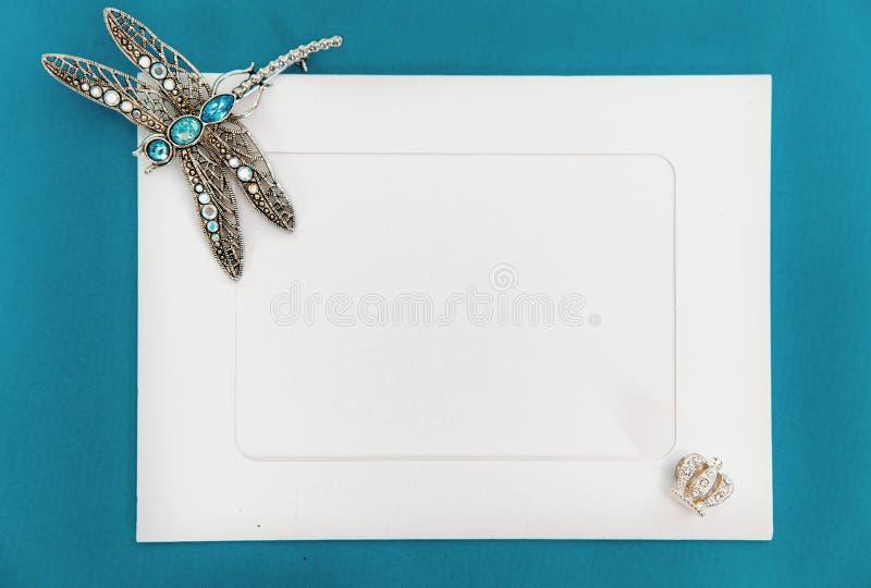 Eine leere Schablone mit Weißbuchrahmen auf dem blauen Hintergrund, verziert mit Schmuck Silberne Libellenbrosche an der Ecke von stockfotografie