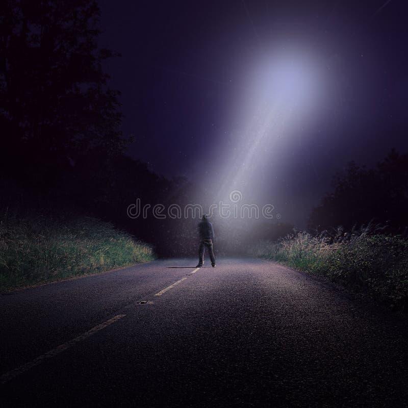 Eine leere Straße nachts mit einer einzigen Zahl, die oben hellem UFO mit einem weißen Lichtstrahl unten kommend betrachtet stockfotografie