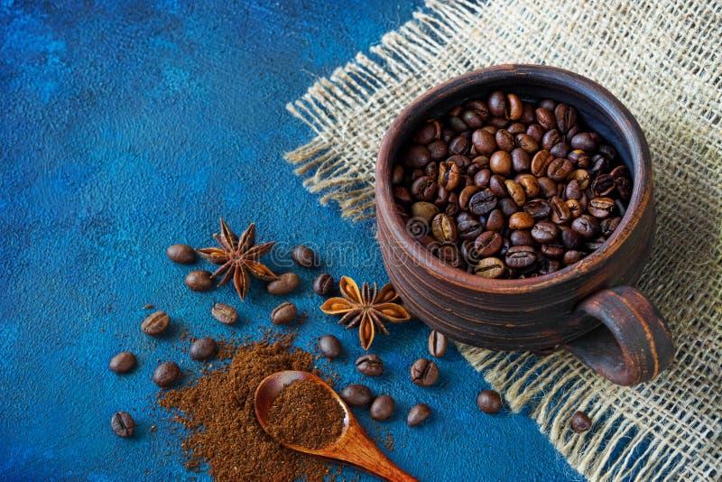 Eine Lehmschale gefüllt mit den Körnern des Kaffees auf dem Tisch stehend, wenn Anissternen und ein hölzerner Löffel mit gemahlen lizenzfreie stockfotos