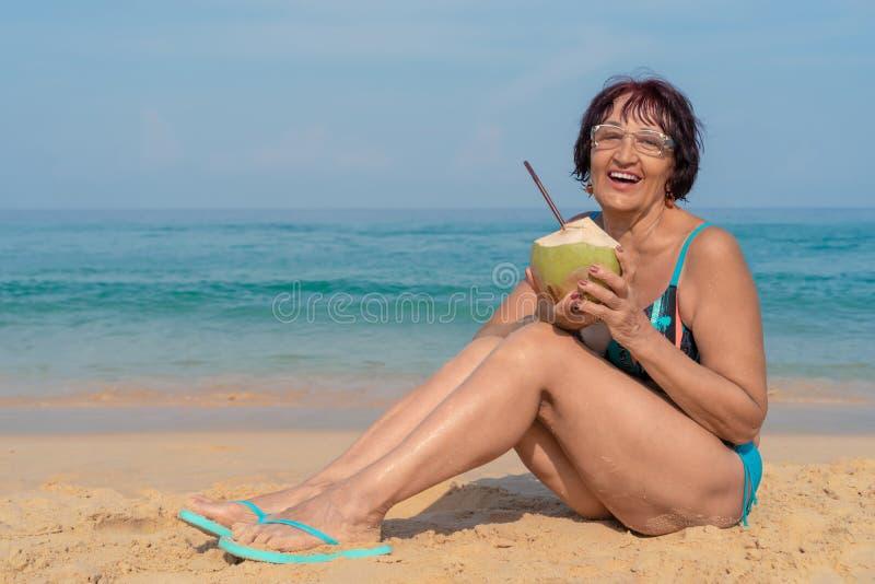 Eine ?ltere Frau mit dem schwarzen Haar sitzt durch das Meer an einem sonnigen Tag stockbild