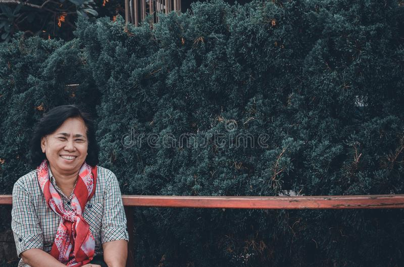 Eine ?ltere Frau sitzt in einem allgemeinen Park stockfotos