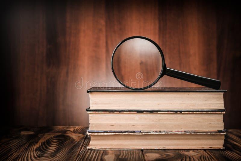 Eine Lupe auf einem Stapel alten Büchern auf einem Holztisch stockbilder